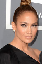 Jennifer Lopez continues to live up to her impeccable celebrity fashion taste with a beautiful black designer dress with a high leg slit and simple diamond stud earrings.